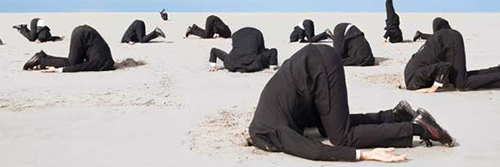 people in black suits on a beach with heads in the sand